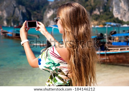 Pretty blonde girl travelling and taking pictures with her phone on beautiful phi phi islands. - stock photo