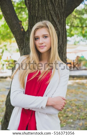 Pretty blonde girl with long hair dreaming in the city. Shy cute young woman in white jacket and red shirt in the park near the tree. Natural beauty woman portrait