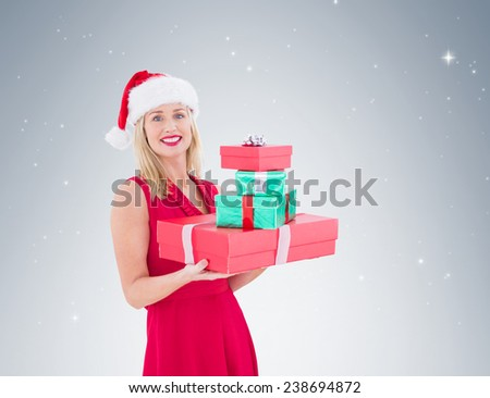 Pretty blonde hoding christmas gifts on vignette background