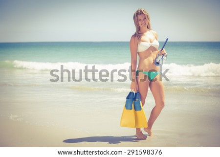 Pretty blonde holding a scuba diving gear on the beach - stock photo