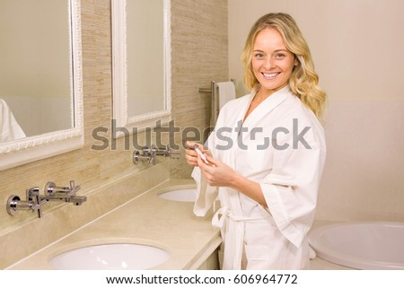 Pretty blonde holding positive pregnancy test in the bathroom