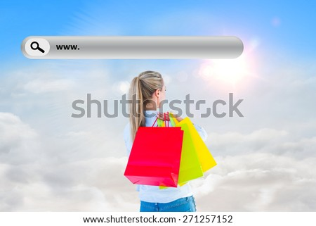 Pretty blonde holding shopping bags against blue sky with white clouds - stock photo