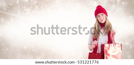 Pretty blonde holding shopping bags against digital composite image of snowflakes