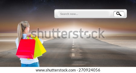 Pretty blonde holding shopping bags against road - stock photo