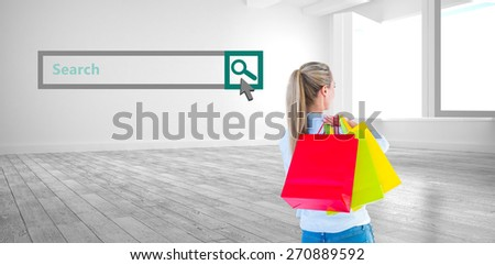 Pretty blonde holding shopping bags against white room with windows - stock photo