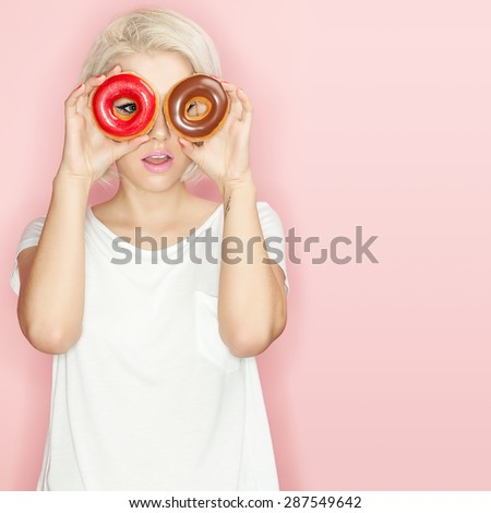 Pretty blonde in a white T-shirt with multi-colored donuts in the hands  - stock photo