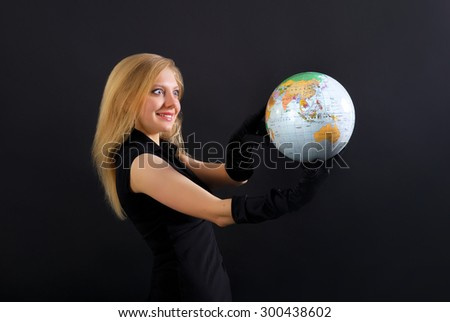 Pretty blonde in black with globe on black background - stock photo