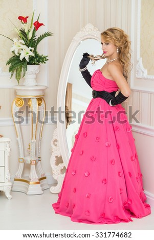 Pretty blonde in long red dress is standing next to the mirror - stock photo