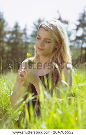 Pretty blonde in sundress sitting on grass holding yellow flower on a sunny day in the countryside