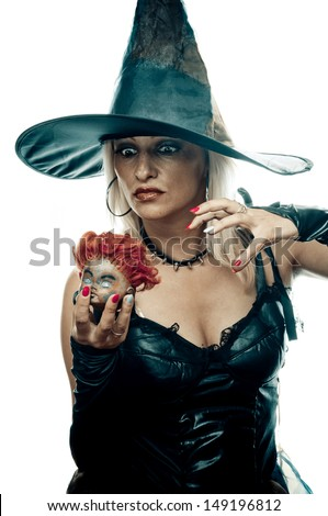 Pretty blonde in the witch costume holding doll head and casts a spell - stock photo