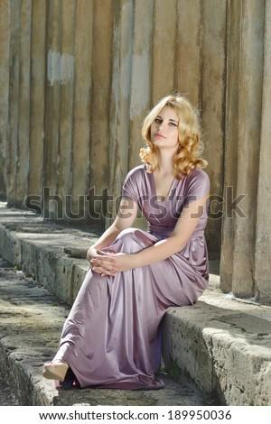 pretty blonde lady near the columns - stock photo