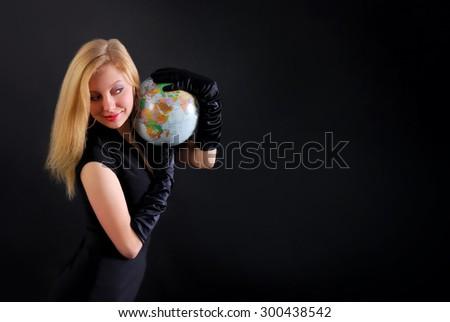 Pretty blonde lady with globe on black background  - stock photo