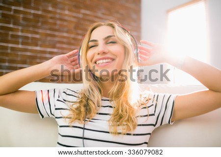 Pretty blonde listening to music on couch at home in the living room - stock photo