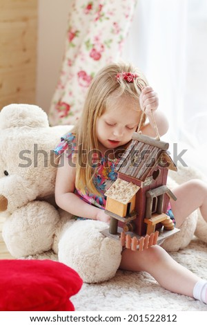 Pretty blonde little girl sits on carpet near window and holds toy house