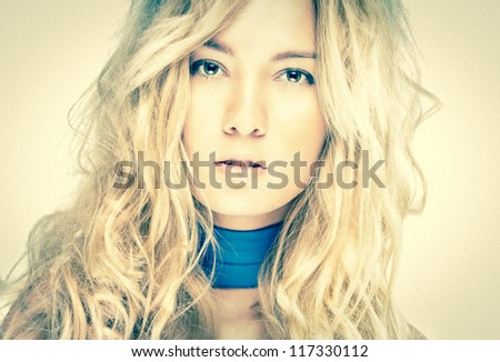 Pretty blonde looking in camera. Beautiful model with perfect skin and wild hairstyle. Attractive young woman with confident look. Sexy face expression of glamorous girl. Gentle and elegant female.