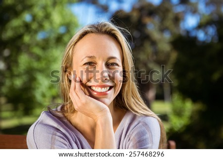 Pretty blonde relaxing in the park on a sunny day - stock photo