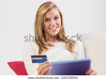 Pretty blonde shopping online with tablet pc at home in the living room - stock photo