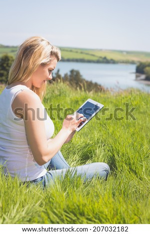 Pretty blonde sitting on grass using her tablet on a sunny day in the countryside - stock photo