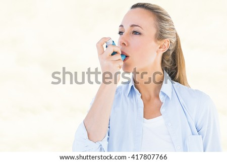 Pretty blonde using an asthma inhaler against yellow background - stock photo