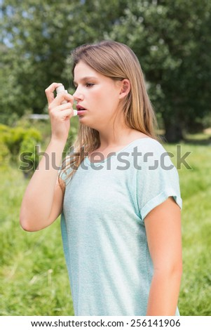 Pretty blonde using an asthma inhaler on a sunny day - stock photo