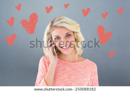 Pretty blonde using her smartphone against grey - stock photo