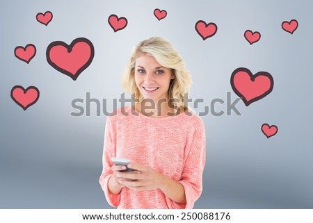 Pretty blonde using her smartphone against grey vignette - stock photo