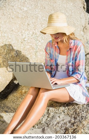 Pretty blonde using laptop at the beach on a sunny day - stock photo