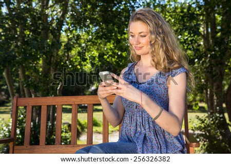Pretty blonde using phone in the park on a summers day