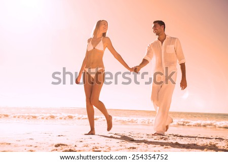 Pretty blonde walking away from man holding her hand on the beach - stock photo