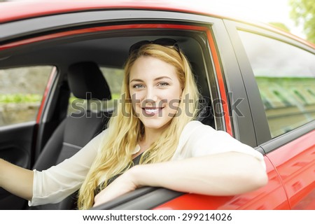 Pretty blonde woman driving a red car. - stock photo