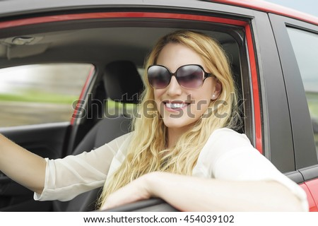 Pretty blonde woman driving a red car, close-up. - stock photo