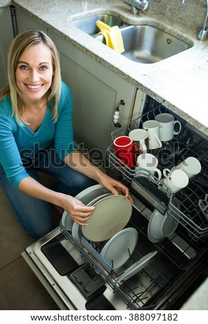 Pretty blonde woman emptying the dishwasher in the kitchen
