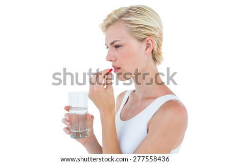 Pretty blonde woman holding glass of water and ready to swallow red pill on white background - stock photo