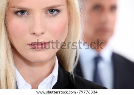 Pretty blonde woman in a suit with an older man out of focus in the background - stock photo