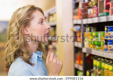 Pretty blonde woman looking at shelves in supermarket - stock photo