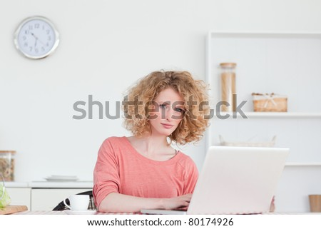 Pretty blonde woman relaxing with her laptop while sitting in the kitchen in her apartment - stock photo