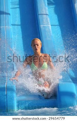 Pretty blonde woman riding down a waterslide - stock photo