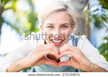 Pretty blonde woman smiling at the camera and doing heart shape with her hands in the park - stock photo