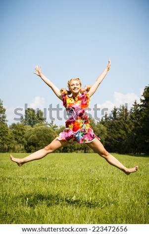 Pretty blonde young girl jumping in a park in a summer