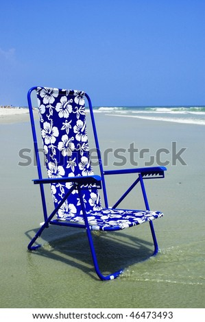 Pretty blue beach chair at surfs edge perfect for cover art - stock photo