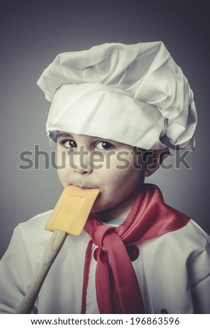 pretty boy dressed as a cook with kitchen utensils - stock photo
