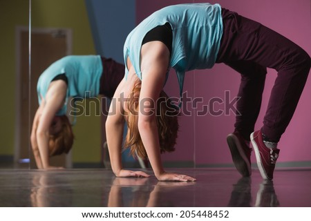 Pretty break dancer doing a back bend in the dance studio - stock photo