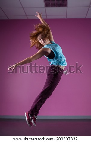 Pretty break dancer leaping mid air in the dance studio - stock photo