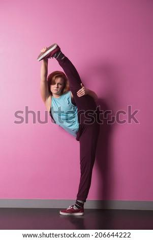 Pretty break dancer lifting her leg above head in the dance studio - stock photo