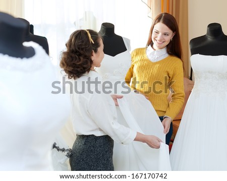 pretty bride chooses bridal dress at wedding store. Shop consultant helps her - stock photo