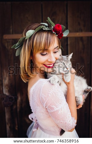 Pretty bride has fun with grey cat posing outside