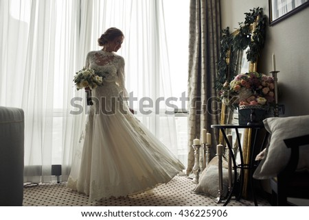 Pretty bride whirls in the morning lights before a mirror - stock photo