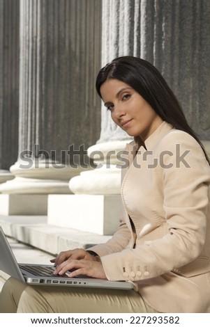 pretty brunette businesswoman typing in laptop  - stock photo