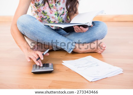 Pretty brunette calculating home finances on the floor at home