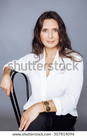 pretty brunette confident mature woman sitting on chair in studio - stock photo